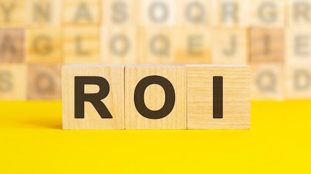 Tekst roi jest napisany na drewnianych kostkach na jasnożółtej powierzchni. w tle rzędy kostek z różnymi literami. pomysł na biznes. roi - skrót od zwrot z inwestycji