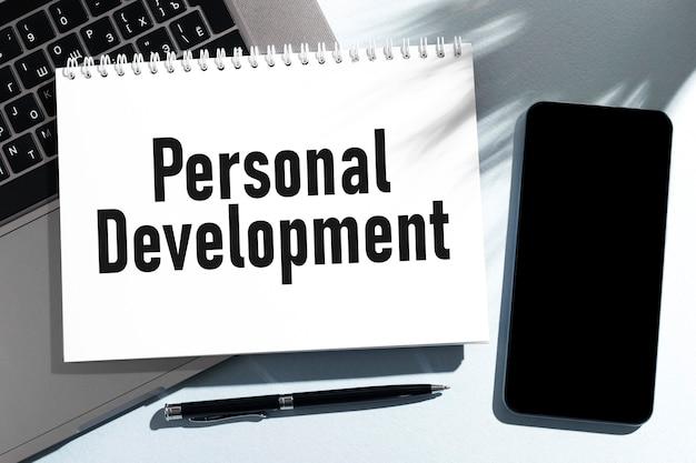 Tekst rozwój osobisty na notebooku, laptopie, telefonie komórkowym. pomysł na biznes. leżał płasko.