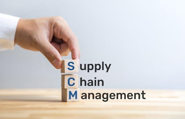 Tekst scm na drewnianym pudełku z męską ręką. zarządzanie biznesem i przemysłem