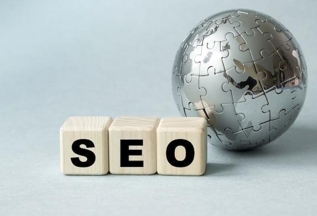 Tekst seo. glob i drewniane kostki na szarym stole. pojęcie globalnej optymalizacji pod kątem wyszukiwarek