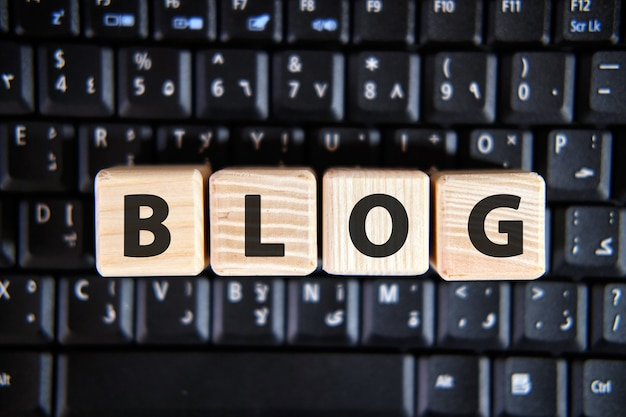 Tekst słowa blog na drewnianych kostkach na czarnej klawiaturze