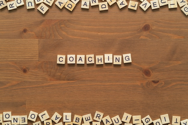 """Tekst słowa """"coaching"""" napisany drewnianymi literami na drewnianym biurku"""