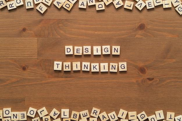 """Tekst słowa """"design thinking"""" napisany drewnianymi literami na drewnianym biurku"""