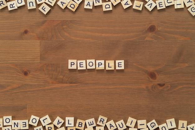 """Tekst słowa """"ludzie"""" napisany drewnianymi literami na drewnianym biurku."""