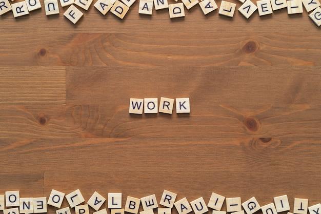 """Tekst słowa """"praca"""" napisany drewnianymi literami na drewnianym biurku"""