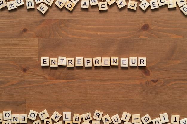 """Tekst słowa """"przedsiębiorca"""" napisany drewnianymi literami na drewnianym biurku."""