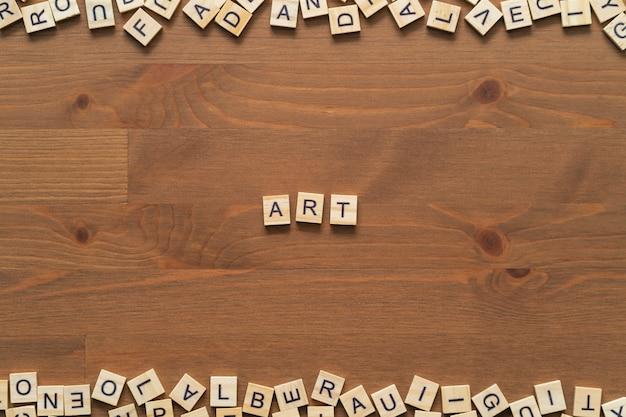 """Tekst słowa """"sztuka"""" napisany drewnianymi literami na drewnianym biurku."""