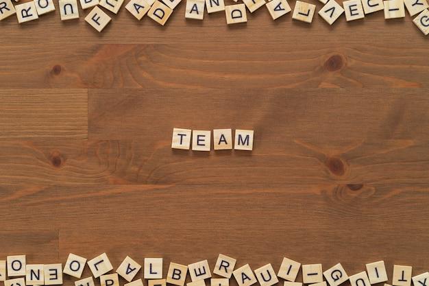 """Tekst słowa """"team"""" napisany drewnianymi literami na drewnianym biurku."""
