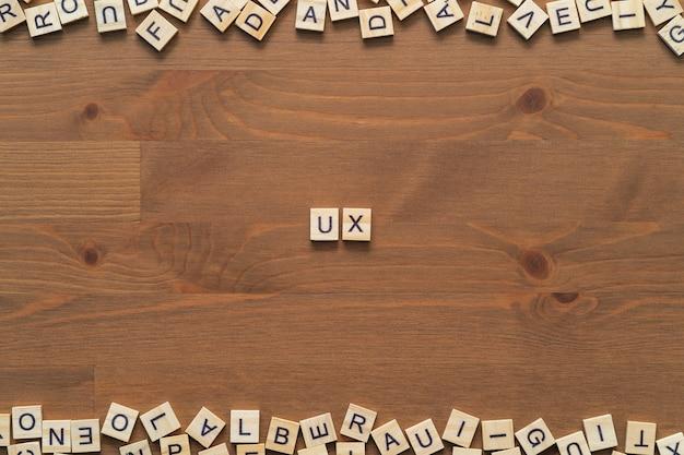 """Tekst słowa """"ux"""" (user experience) napisany drewnianymi literami na drewnianym biurku."""