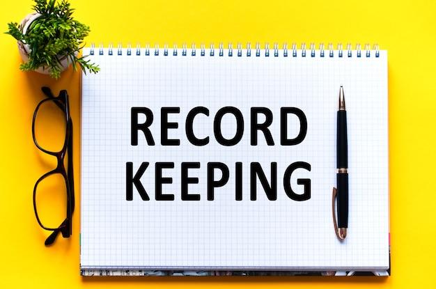 Tekst słowny przechowywanie rekordów na białej karcie papieru, czarne litery. pióro, okulary i zielony kwiat na żółtym tle. pomysł na biznes. koncepcja edukacji.