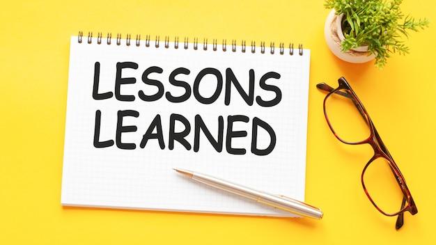Tekst słowo lekcje nauczone na białej karcie papieru, czarne litery. pióro, okulary i zielony kwiat na żółtym tle. pomysł na biznes. koncepcja edukacji