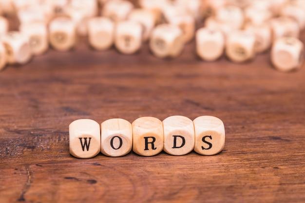 Tekst słowo na drewnianych kostkach nad biurkiem brązowy