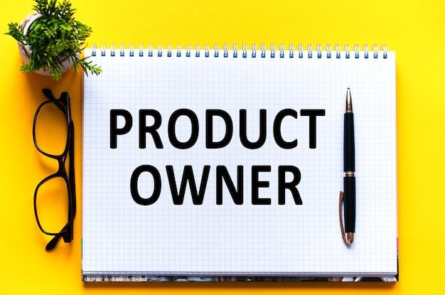 Tekst słowo właściciel produktu na białej karcie papieru, czarne litery. pióro, okulary i zielony kwiat na żółtej ścianie. pomysł na biznes. koncepcja edukacji.