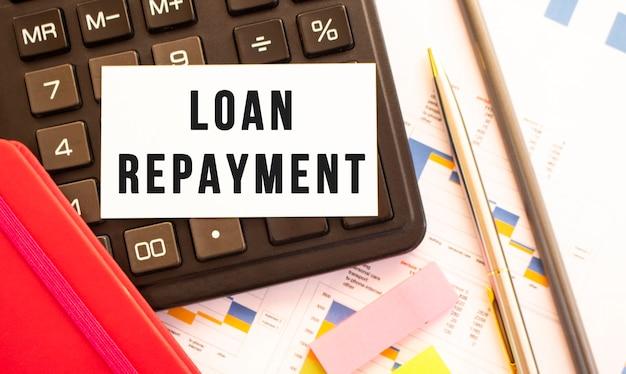 Tekst spłata pożyczki na białej karcie z metalowym długopisem, kalkulatorem i wykresami finansowymi. koncepcja biznesowa i finansowa