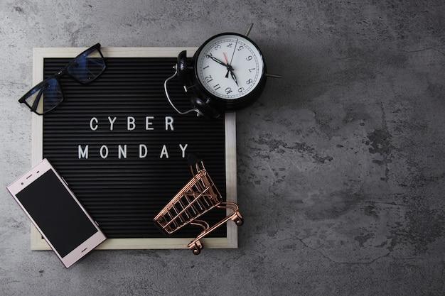 Tekst sprzedaży płaskiej świeckiej w cyber poniedziałek na tablicy z torbą z budzikiem i gadżetem