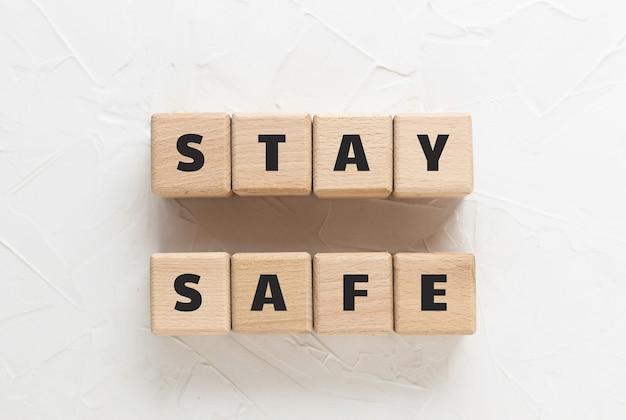Tekst stay safe wykonany z drewnianych kostek na białym, teksturowanym tle. kwadratowe bloki drewniane. widok z góry, płaski układ.