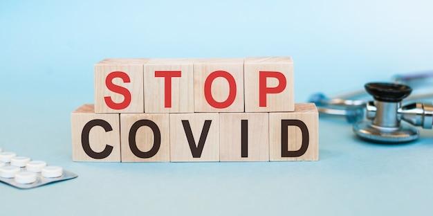 Tekst stop covid-19 na drewnianych kostkach z tabletkami i stetoskopem. powstrzymaj globalną pandemię koronawirusa.
