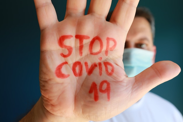 Tekst stop covid-19 w ręce mężczyzny, europejczyk ostrzegający przed koronawirusem