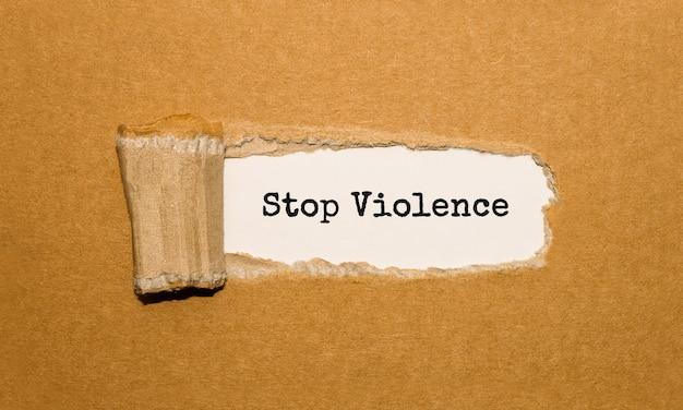 Tekst stop violence pojawiający się za podartym brązowym papierem