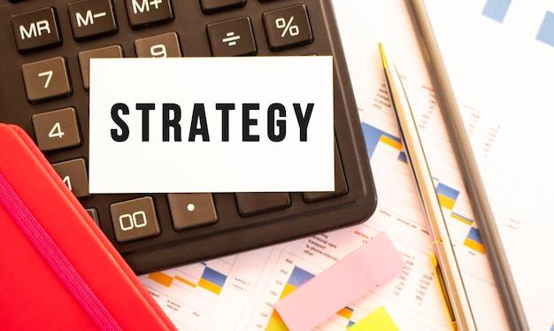 Tekst strategia na białej karcie z metalowym długopisem, kalkulatorem i wykresami finansowymi