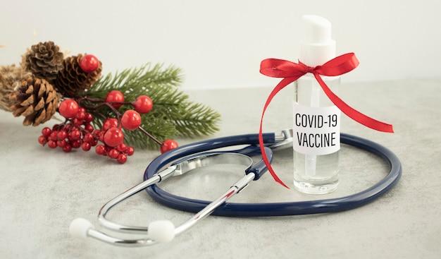 Tekst szczepionki covid-19 na słoiku z czerwoną wstążką, koncepcją nowego roku i szczepieniem covid