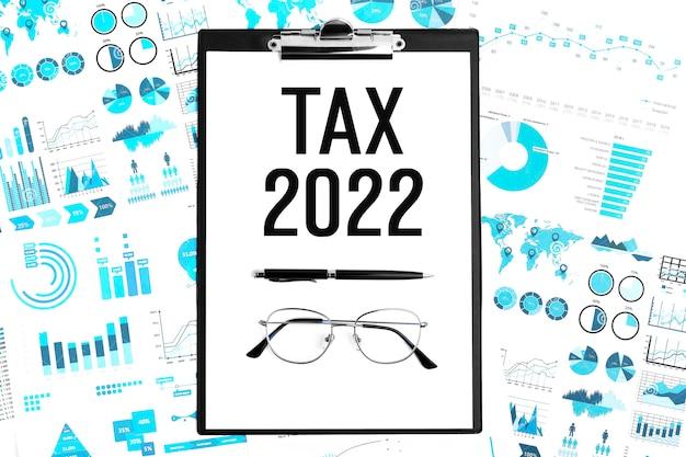 Tekst tax 2022 w schowku, długopisie, okularach, wykresie, wykresach. leżał płasko. koncepcja planowania odliczeń podatkowych.