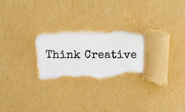 Tekst think creative pojawiający się za podartym brązowym papierem