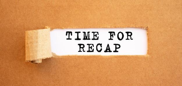 Tekst time for recap pojawiający się za rozdartym brązowym papierem