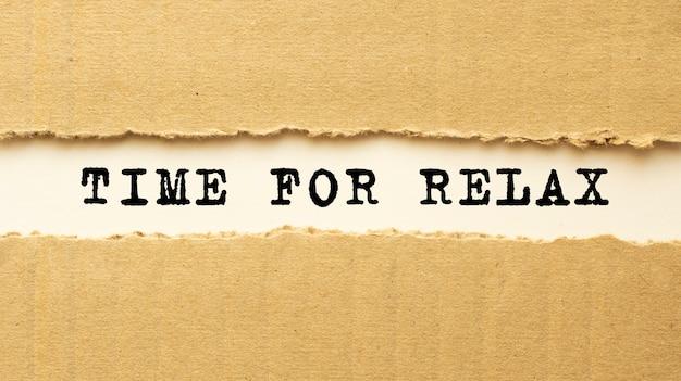 Tekst time for relax pojawiający się za rozdartym brązowym papierem. widok z góry.
