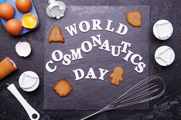 Tekst to światowy dzień kosmonautyki i ciasteczka w postaci astronauty, rakiety, latającego spodka i kosmity.
