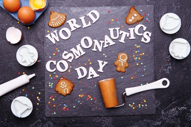 Tekst to światowy dzień kosmonautyki i ciasteczka w postaci astronauty, rakiety, latającego spodka i kosmity
