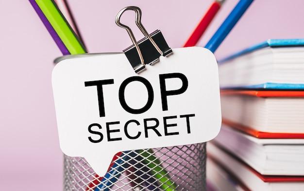 Tekst top secret na białej naklejce z tłem papeterii biurowej. mieszkanie leżało na koncepcji biznesu, finansów i rozwoju