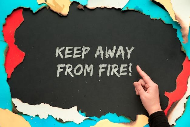 """Tekst """"trzymaj z dala od ognia"""" w spalonej papierowej ramce z białym, czerwonym, żółtym i niebieskim papierem z wypalonymi krawędziami, czarną papierową ścianą, rękami pokazującymi znak ok i wskazującymi na znak."""