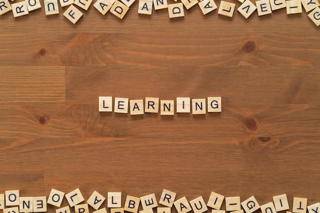 """Tekst """"uczenia się"""" napisany drewnianymi literami na drewnianym biurku."""