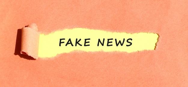 Tekst umieszczony na żółtym papierze za podartym kolorowym papierem. widok z góry.