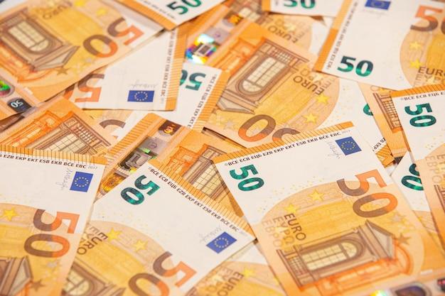 Tekst w tle pięćdziesięciu banknotów euro.
