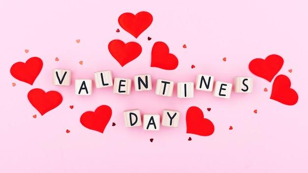 Tekst walentynki na drewnianym bloku. kartki okolicznościowe na różowym tle, kartka ozdobiona wzorem czerwonych serc, walentynki