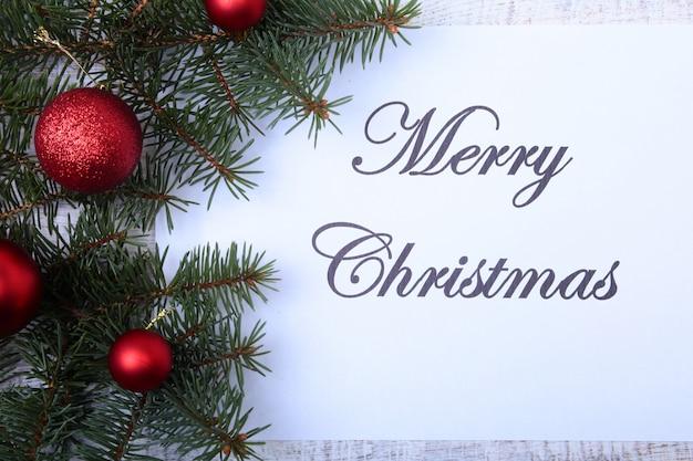 Tekst wesołych świąt na papierze z choinkowe, gałęzie, kolorowe szklane kulki, dekoracji i szyszki na drewnianym