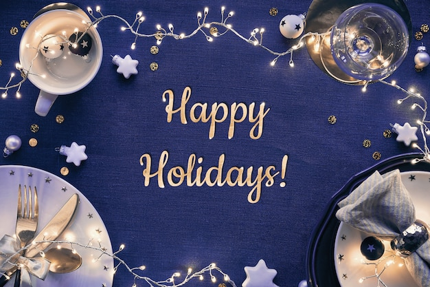 Tekst wesołych świąt. świąteczny stół z białymi talerzami, złotymi naczyniami i ciemnoczerwonymi złoconymi dekoracjami. rozłożony na płasko, widok z góry na granatowej lnianej tkaninie.
