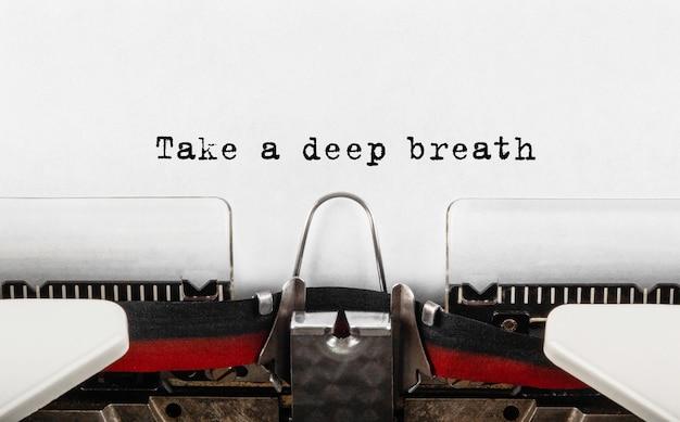 Tekst weź głęboki oddech wpisany na retro maszynie do pisania.