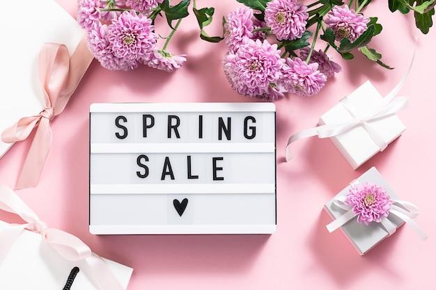Tekst wiosenna wyprzedaż na lightboxie z obecnymi pudełkami, torbami, wstążkami i kwiatami