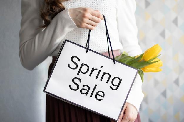 Tekst wiosenna wyprzedaż na lightboxie z prezentową torbą i pięknymi kwiatami w pastelowych kolorach. świąteczna wyprzedaż i baner promocyjny.