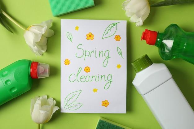Tekst wiosenne porządki, narzędzia do czyszczenia i tulipany na zielono