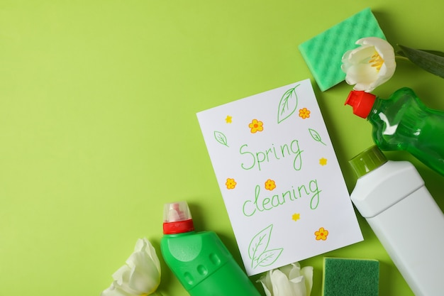 Tekst wiosenne porządki, narzędzia do czyszczenia i tulipany na zielonym tle