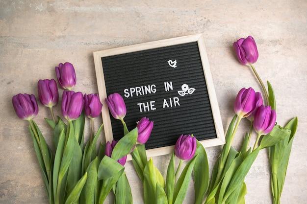 Tekst wiosenny w powietrzu na tablicy z listami i bukietem fioletowych tulipanów