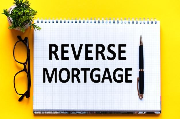 Tekst word reverse hipgage na białej karcie papieru, czarne litery. pióro, okulary i zielony kwiat na żółtej ścianie. pomysł na biznes. koncepcja edukacji.