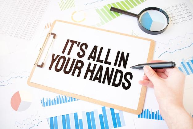 Tekst wszystko jest w twoich rękach na białej kartce papieru i markerem na dłoni biznesmena na schemacie.