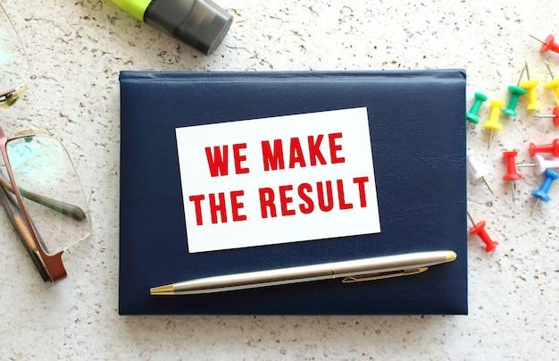 Tekst wykonujemy wynik na wizytówce leżącej na niebieskim zeszycie obok okularów i papeterii. pomysł na biznes.