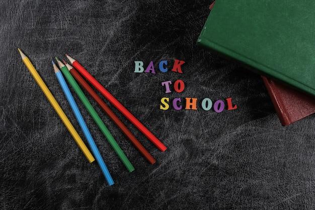 Tekst z powrotem do szkoły z kolorowych listów, książek, kredki na tle tablicy kredowej. widok z góry