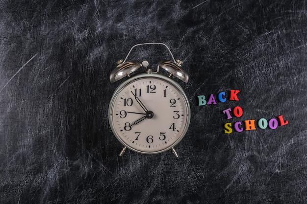 Tekst z powrotem do szkoły z kolorowych liter i budzika na tle tablicy kredowej.
